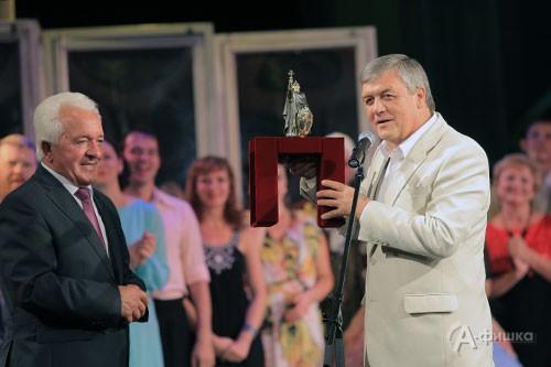 Мэр города Белгорода Сергей Боженов вручает юбиляру статуэтку с симовлом города